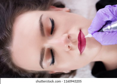 Young woman having permanent makeup on lips in beautician salon. Tattoo red pigment on lips with instrument and purple protective gloves. Close up, selective focus