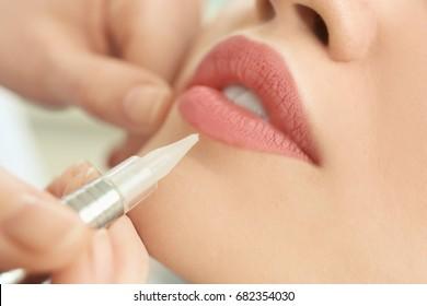 Young woman having permanent makeup on lips in beautician salon, closeup