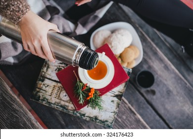 Young woman having picnic: drinking tea and reading book