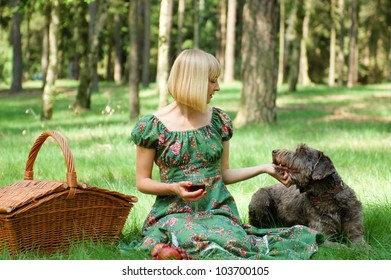 Young woman having a picnic in the wood with a dog
