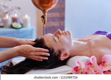 Young woman having pouring oil massage  spa treatment. Shirodhar