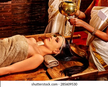 Young woman having pouring oil Ayurveda spa treatment.