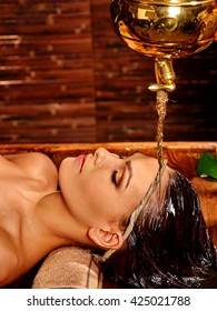 Young woman having pouring oil massage in India spa treatment. Shirodhara Pouring oil on head. Treatment of head.