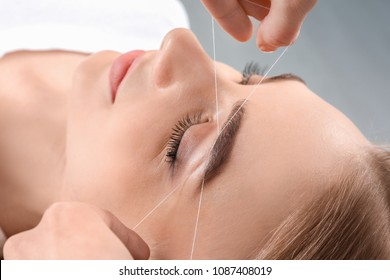 Young woman having professional eyebrow correction procedure in beauty salon