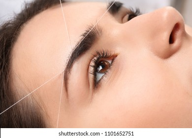 Young woman having professional eyebrow correction procedure, closeup