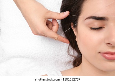 Young woman having professional eyebrow correction procedure in beauty salon, closeup