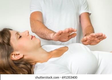 Young woman having reiki healing treatment - alternative medicine concept