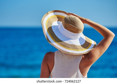 Young woman having a rest at the seacoast. She is touching her bonnet hat.