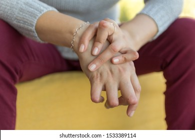 Young woman having rheumatoid arthritis takes a rest, sitting. Hands and legs are deformed. She feels pain. Selected focus.