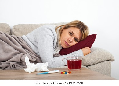 Young woman having seasonal influenza is resting on thesofa, drinking hot tea and taking medication