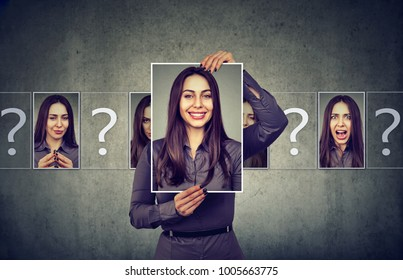 Young woman having split personality while posing with photos of different emotions.