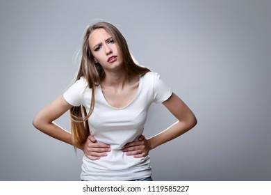 Young woman having stomach ache on grey background