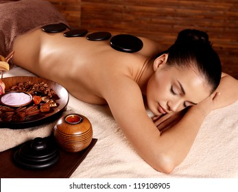 Young woman having stone massage in spa salon. Healthy lifestyle.