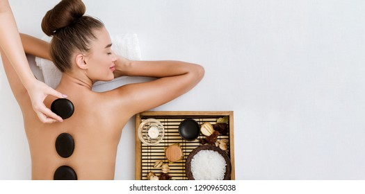 Young woman having stone massage in spa salon, top view, copy space