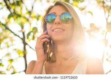 Young woman having a telephone chat with a friend, enjoying a day in the park