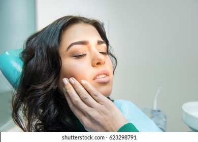 Young woman having toothache. Sad lady at the dentist. Gum disease symptom.