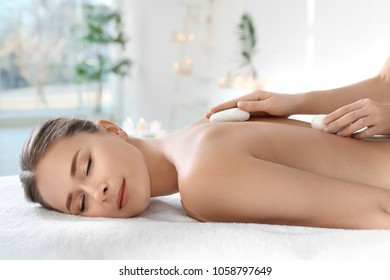 Young woman having traditional hot stones massage in spa salon