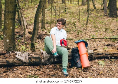 Young woman having trouble feeling knee pain during travel in forest. Injury on way to camp. female tourist got leg injury in forest and gets hurt. Health problem in journey. Theme Insurance Company.