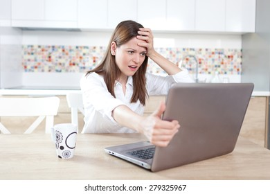 Young woman having trouble with laptop
