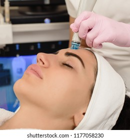 Young woman having ultrasound face peeling in spa salon