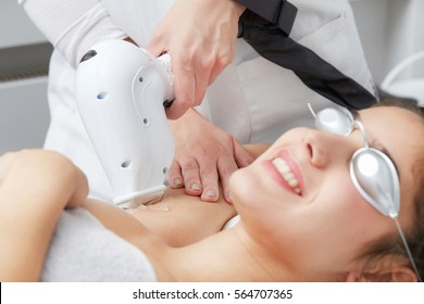 Young woman having underarm laser hair removal treatment in salon