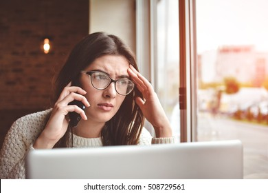 Young woman is having unpleasant conversation on mobile phone with her husband, because of jealousy. Concerned female have in bad mood is talking on cell telephone while sitting alone in coffee shop