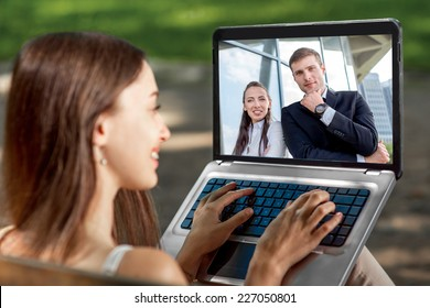 Young woman having video call with her business friends on laptop at the park