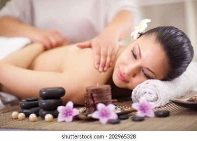 young woman having a wellness back massage at spa salon