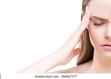 A young woman with a headache holding head, isolated on white background with copy-space.