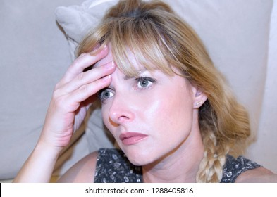 Young woman with headache holding and massage head. Miserable anxious close up face of girl suffer from pain in head