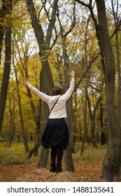 Young woman in headphones dancing in the park in autumn