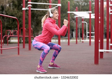 Young woman with headphones listening to music and exercising on sports ground