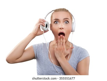 Young woman with headphones listening music, shocked, isolated on white