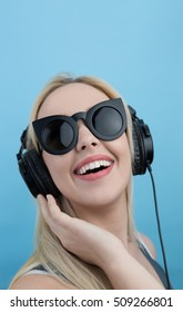 Young woman with headphones  listening to music and having fun against blue background