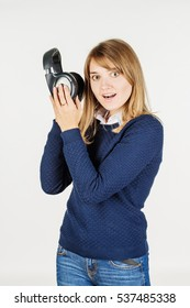 Young woman with headphones listening music on white background