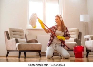 Young woman with headphones and mop ready for home cleaning