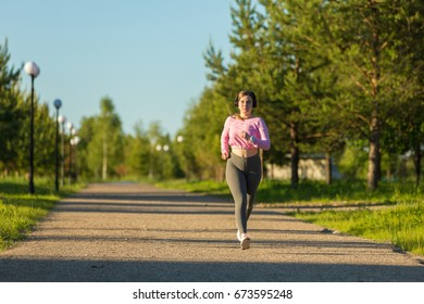 Young woman with headphones run in the Park