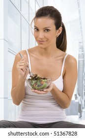 Young woman at health club with a salad