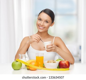 young woman with healthy breakfast and measuring tape