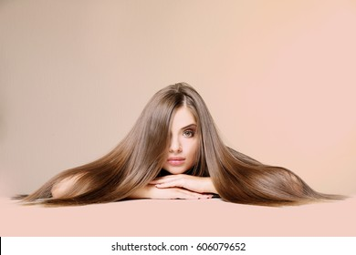 Young woman with healthy hair on color background