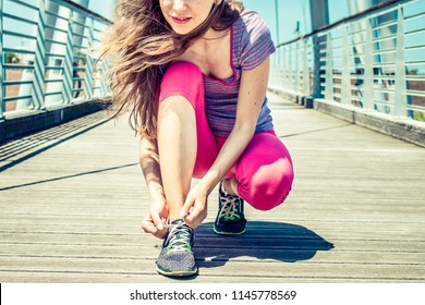 young woman healthy lifestyle concept. jogging girl tie shoe laces on her sport shoes getting ready to run. close up on sporty lady doing fitness