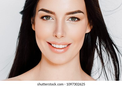 Young woman with healthy teeth smile natural portrait, beautiful female girl with healthy skin and long brunette hair. Studio shot.