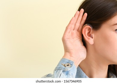 Young woman with hearing aid on color background