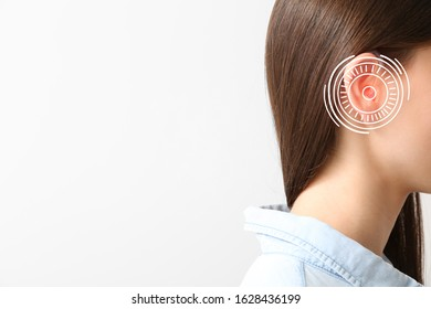 Young woman with hearing aid on light background