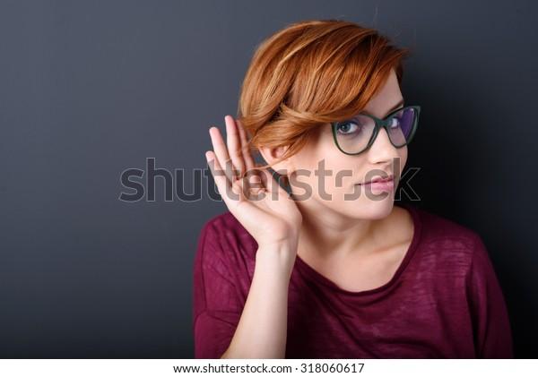 Junge Frau mit einer Hörstörung oder Hörverlust, die ihre Hand hinter ihrem Ohr mit dem Kopf beiseite gekehrt, um zu versuchen, den verfügbaren Ton zu ihrer Ohrtrommel zu verstärken und zu lenken