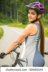 Young woman in helmet standing with her bicycle on the forest road. Rear view.