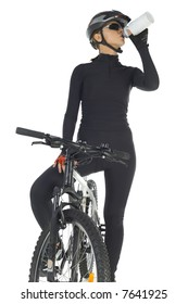 Young woman with helmet and sunglasses, sitting on mountain bike and drinking. White background, front view