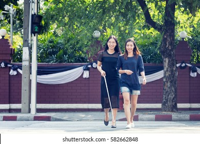 Young Woman Helping Blind Woman crossing the road