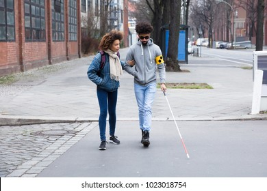 Young Woman Helping Blind Man With White Stick While Crossing Road