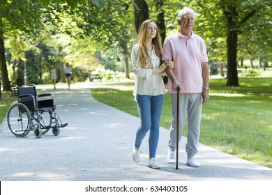 Young woman helping elderly man with walking with cane in the park